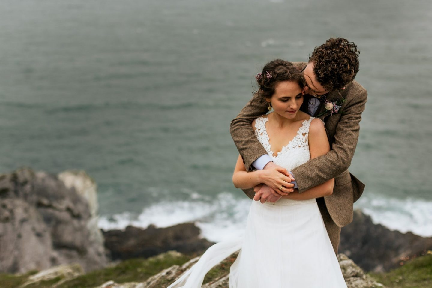 Groom hugging his bride from behind on cliff edge Inish Beg