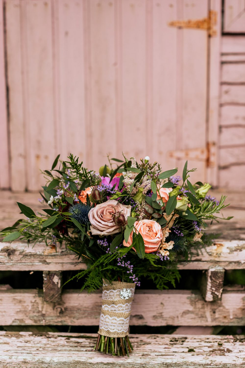 Wild flower wedding bouquet on pink distressed wooden steps