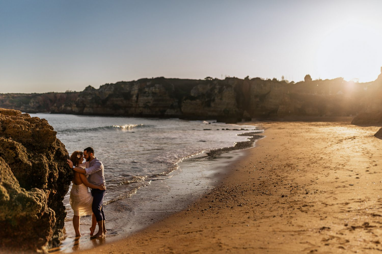 wedding couple leaning against rocks on a beach