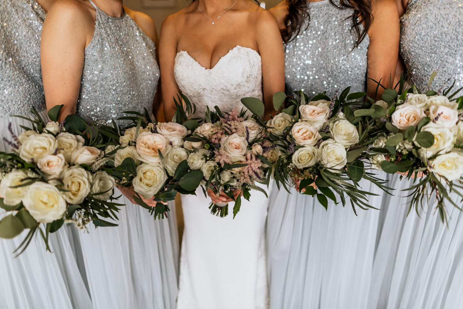 Four bridesmaids and bride holding five rose bouquets