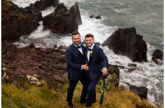 Two gay men standing on a cliff on their wedding day in dingle