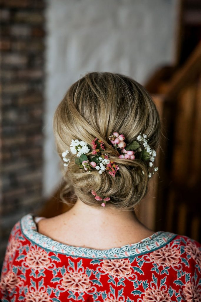 Blond bridal hair styled into soft chignon with pink and white flowers