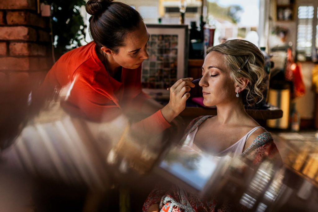 Eyeliner being painted onto a bride by make-up artist