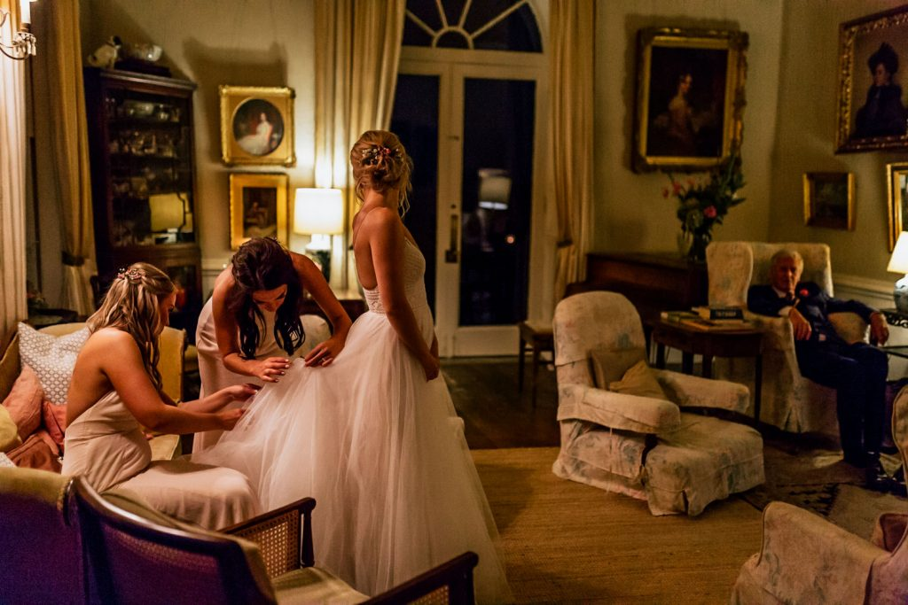 Bridesmaids fixing train of Wtoo by Waters dress