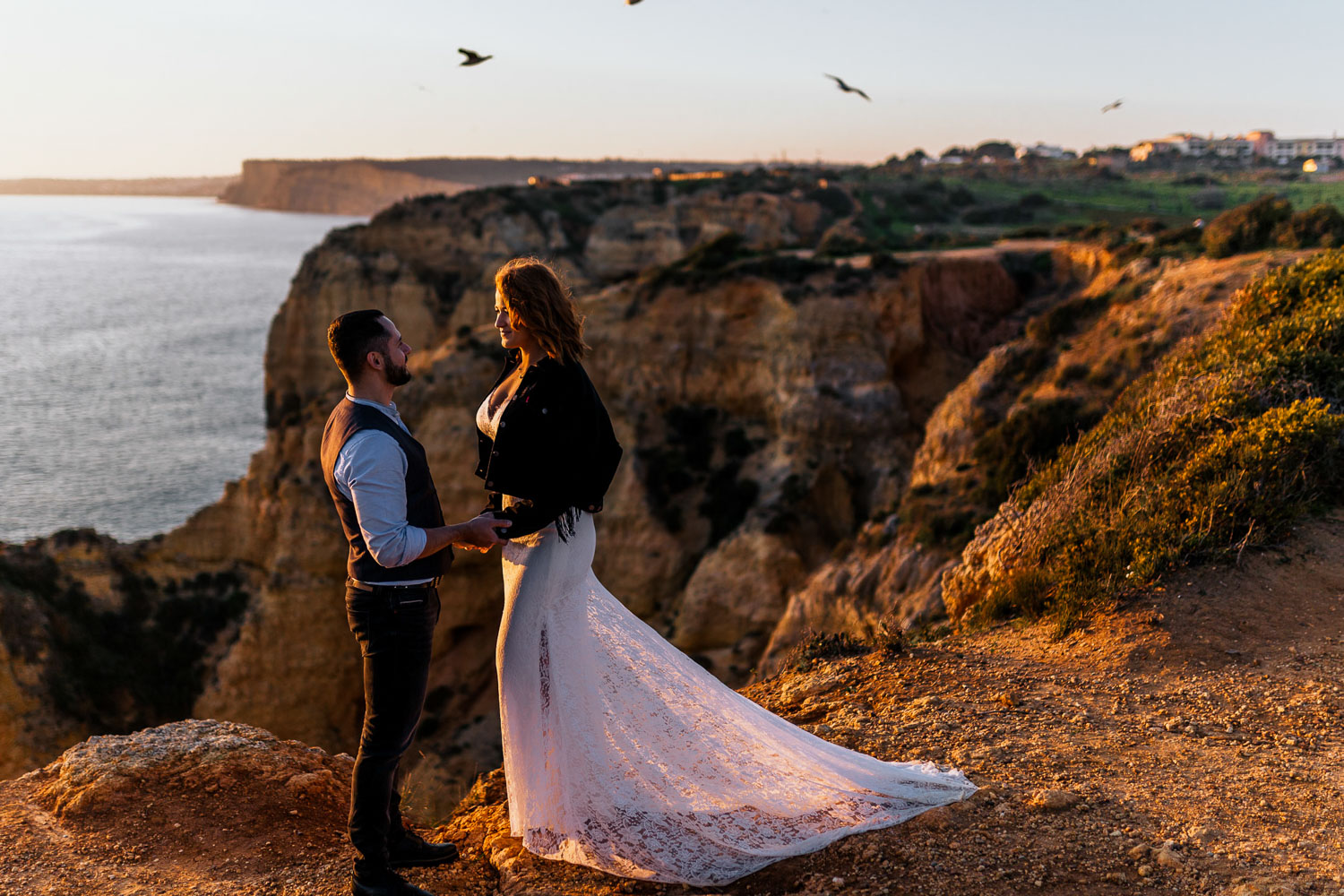 Couple on cliffs on their wedding day at sunset, Algarve